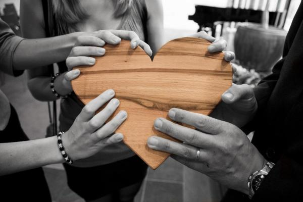 group of people holding a wooden heart